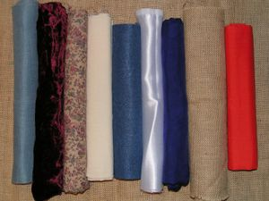 A variety of fabric.  From the left: evenweave cotton, velvet, printed cotton, calico, felt, satin, silk, hessian, polycotton.